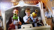 Two boys use their spring-action shooters on Toy Story Mania!