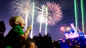 A excited young boy sits on his dad's shoulders and points to the exploding Disneyland Park fireworks