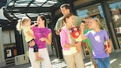 A mother and father laugh alongside their 4 children after exiting AMC Downtown Disney 12 Theatres