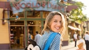 A woman with a Mickey backpack smiles while walking past the World of Disney store