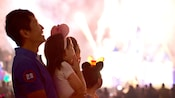 A happy family watches with glee while a frenzy of fireworks lights up the night at Disneyland Park