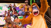 A trumpeter plays while King Louie dances during the Mickey and the Magical Map show