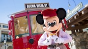Train conductor Mickey Mouse stands in front of a vintage train car with a destination sign that reads Buena Vista Street