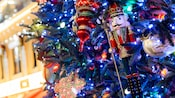 Illuminated Christmas lights, assorted glass bulbs, a nutcracker ornament and a snowflake ornament adorn a tree