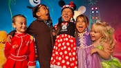 Five young children in costumes laugh and shout while enjoying Mickey's Halloween Party