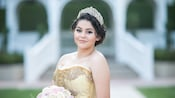 A young woman in a quinceñera gown and tiara poses in an outdoor setting holding a bouquet of roses