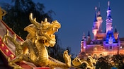 Dragon statues adorn a Shanghai Disneyland rooftop with the Enchanted Storybook Castle in the background