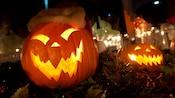 Glowing and grimacing Jack-o'-lanterns with jagged teeth