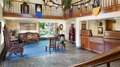 Castle Inns lobby features a check in desk, stained glass window, iron chandelier and medieval décor