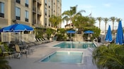 Lounge chairs and umbrellas line the pool and spa at Hampton Inn & Suites