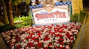 A patch of flowers in front of a sign for Disney's Paradise Pier Hotel