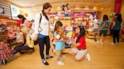 A girl holding a teddy bear and her mother talk to Cast Member at Build-A-Bear Workshop