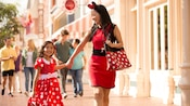 A mother and daughter wearing Minnie-themed outfits walk hand-in-hand down Main Street, U.S.A.