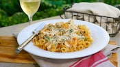 A delicious plate of chicken sun dried tomato pesto pasta with grated cheese sits on an outdoor table with a glass of wine