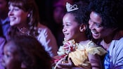 A young girl dressed as Belle sits on her mom's lap as they smile during a performance of Fantasmic!