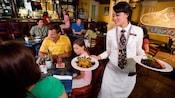 A Ralph Brennan's Jazz Kitchen server carries a full dinner plate in each hand