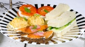 Watercress, salmon gravlax and other classic tea sandwiches are arranged on a striped serving platter