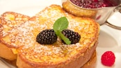 A plate of Steakhouse 55 French Toast topped with powdered sugar and fresh berries