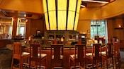 Elegant wood bar and high-backed chairs at Napa Rose Lounge