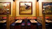 Storyteller's Cafe dining booth beneath a painting of pioneers on horseback
