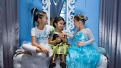 Young female Guests smile after undergoing magical transformations into Anna and Elsa from 'Frozen'