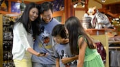 A family of 4 looks at a cell phone while inside World of Disney in Downtown Disney District
