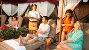 A waitress delivers a drink to a man on a chaise lounge next to his wife and daughter in a cabana