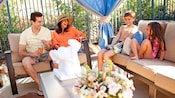 A family of four, dressed for the pool, laughs while sitting on sofas in a cabana