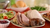Portions of beef, sliced ham and turkey fill a platter surrounded by plates with various side dishes