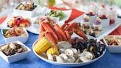 Plato de patas de cangrejo, almejas, mejillones, maíz en mazorca y papas, junto a otros platos de comidas