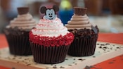 3 chocolate cupcakes, 1 with white frosting and red sprinkles topped with a Mickey Mouse image