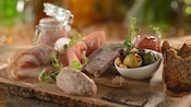 A charcuterie assortment arranged on a wooden plank includes carpaccio, prosciutto, 2 types of pâté and a small bowl of mixed olives