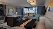 Una cabina y una mesa cerca de un bar, un microondas, un horno y un área de estar con un sofá, una ventana y una TV