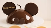 A chocolate cake designed to resemble Mickey Mouse, inscribed with the message 'Happy Birthday'