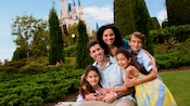 A family of five hug while posing in a lush garden with Cinderella Castle in the background