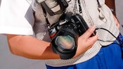 Un photographe Disney PhotoPass portant un appareil photo à téléobjectif dans le creux de son bras