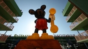 The back of a giant plastic statue of Mickey Mouse holding a telephone receiver