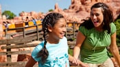 2 girls smiling and holding on to each other as they disembark Big Thunder Mountain Railroad