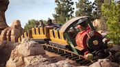 An Old West locomotive speeds around a turn at Big Thunder Mountain Railroad in Disneyland