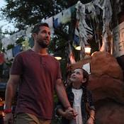 Un homme et une jeune fille marchent près de drapeaux, d'un rocher et d'enseignes indiquant «Everest Expedition» et «Trekkers Travelers Visitors Beware».