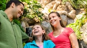 A father and his 2 daughters on Discovery Island Trails at the base of The Tree of Life