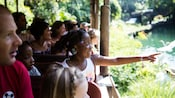 A girl points at animals while riding in a bus full of Guests on Kilimanjaro Safaris