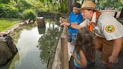 A Wilderness Explorer Troop Leader directs 2 kids to look across a moat