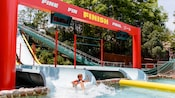 A boy in an inner tube fist-pumps in triumph at the finish of Downhill Double Dipper
