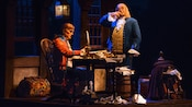 Benjamin Franklin stands across from a seated Thomas Jefferson onstage at The American Adventure