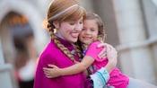 A smiling Princess Anna hugs a little girl