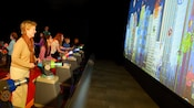 5 Guests ranging in age from preteen to adult play a shooting gallery game at Innoventions East