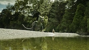 A scene from the Disney movie Pete's Dragon features a young boy and a large dragon on the shore of a lake in a forest