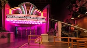 Loading platform for The Great Movie Ride attraction with a marquee and neon lights
