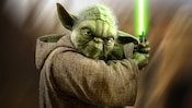 Yoda holds his lightsaber in a fighting stance